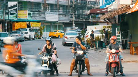 minibus : PATTAYA, THAILAND - DECEMBER 16, 2017: Girls and men on motobikes wait their turn to turn into traffic. Huge traffic on the streets of Thailand. A lot of cars, minibuses, motorcycles drive in a typical large Asian street Stock Footage