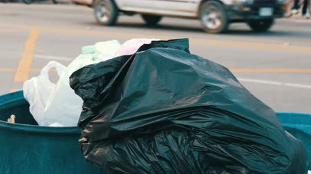 green soda can : PATTAYA, THAILAND - DECEMBER 16, 2017: Full garbage can with large garbage bags full of leftover food and waste is on the street