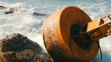 lifebelt : Large yellow buoy on the shores of azure sea. The waves hit the buoy and the big rocks on the shore Stock Footage