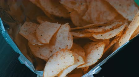 colesterol : Potato chips in package on the table. Female hand takes chips Stock Footage