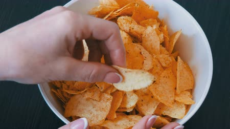 colesterol : Beautiful well-groomed hands of the women take potato chips. Potato chips close up view