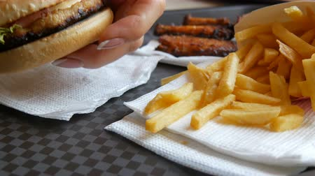 bacon burger : Womans hand takes a burger, next to the tray are roasted chicken wings and French fries. Fast food restaurant