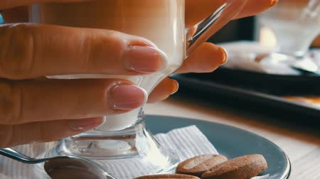 latte macchiato : Glass beaker with coffee, graded from dark brown to milky white. Beautiful latte with a big foam in the cafe. A woman touches a glass with a hot latte Stock Footage