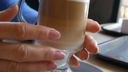 brew coffee : Glass beaker with coffee, graded from dark brown to milky white. Beautiful latte with a big foam in the cafe. A woman touches a glass with a hot latte Stock Footage