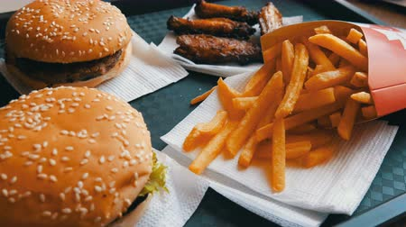 batatas fritas : Hands of a teenager take french fries. Burgers, chicken wings, french fries on tray in a fast food restaurant. Unhealthy food