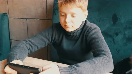 boyish : Boy teen playing on black smartphone in a stylish cafe Stock Footage
