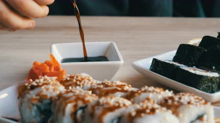 sake : Tasty beautiful large white and black sushi rolls from Japanese cuisine stand on platter on the table in the restaurant. Soy sauce is poured into a saucer Stock Footage
