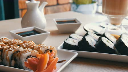 нигири : Two sets of sushi rolls in a stylish, beautifully decorated cafe. Restaurant Japanese cuisine on the table next to sushi porcelain teapot for soy sauce and saucer