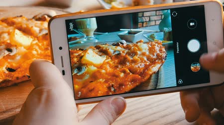 основное блюдо : Teenager boy takes a photo of food on a smartphone. Italian pizza on the restaurant table
