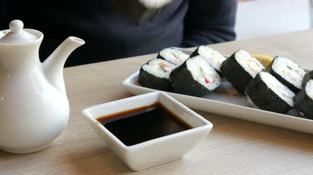 nori : A teenager boy takes sushi roll with Chinese bamboo sticks and drops it into soy sauce, takes a piece of pink ginger. Japanese cuisine on white porcelain plate next to green wasabi ginger and sauce Stock Footage