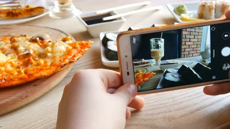 основное блюдо : Teenager boy takes a photo of food on a smartphone. Japanese sushi rolls and Italian pizza on the restaurant table Стоковые видеозаписи