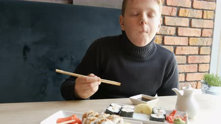 sushi bar : A teenager boy takes sushi roll with Chinese bamboo sticks and drops it into soy sauce, takes a piece of pink ginger. Japanese cuisine on white porcelain plate next to green wasabi ginger and sauce Stock Footage