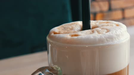 brew coffee : Coffee latte with milk and air foam and a black straw stands in a transparent special glass on the table in stylish cafe Stock Footage