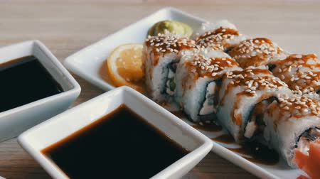 soya : Large beautiful white sushi rolls with eel cucumber Philadelphia cheese ginger wasabi and a slice of lemon from Japanese cuisine next to soy sauce in special saucer Stock Footage
