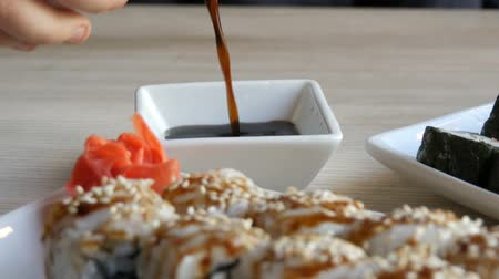 seafood recipe : Japanese food. Sushi rolls lie on the table next to ginger wasabi and lemon. Soy sauce is poured from a special porcelain teapot in saucer