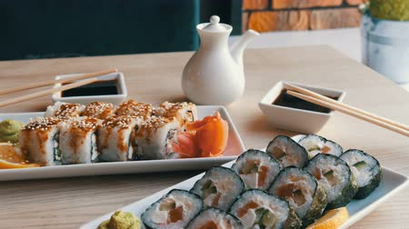 васаби : Two sets of sushi rolls in a stylish, beautifully decorated cafe. Restaurant Japanese cuisine on the table next to sushi porcelain teapot for soy sauce and saucer