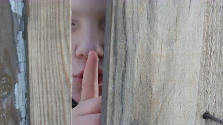 boyish : Frightened teenager boy peeks through a gap between a fence or a doorway and shows a finger of a sign of silence, applying his index finger to his lips