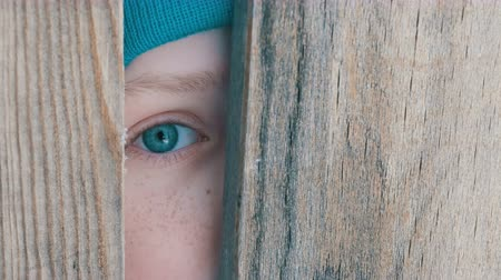 boyish : Frightened eye of a teenage boy peeks into the door slot or crevice in the fence
