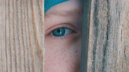 boyish : Unusual turquoise eye of a teenage boy full of tears looks through the doorway or a slot in the fence directly into the camera. The child peeps
