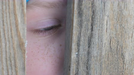 kapualj : Frightened eye of a teenage boy peeks into the door slot or crevice in the fence