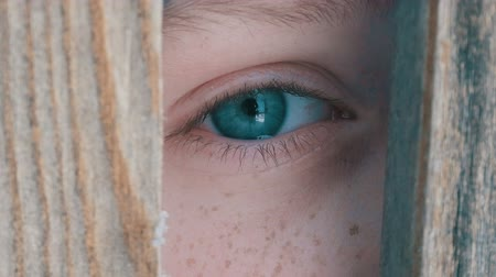 boyish : Boy teenager peeking into the crack in fence or doorway close up view Stock Footage