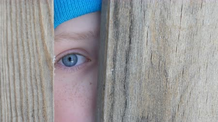 boyish : Frightened blue eye of a teenage boy peeks into the door slot or crevice in the fence