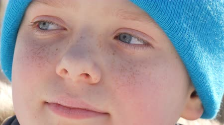 freckles : Boy teenager with sky blue eyes and freckles on his face in a blue hat looks into distance