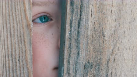 dětinský : Boy teenager peeking into the crack in fence or doorway