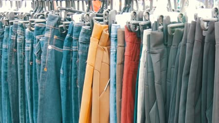 воротник : Pants hang on hanger, women look at clothes and choose. Flea market, clothes sold on the market