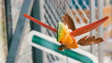 malom : Wooden windmill kinetic sculpture of colorful bird develops in the wind Stock mozgókép