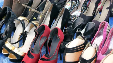 usado : PATTAYA, THAILAND - DECEMBER 16, 2017: Flea market in Thailand. People choose things on a flea market. Many second-hand things on the floor. A lot of toed shoes with heels and different colors Stock Footage