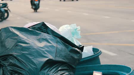 green soda can : Full clogged trash can with plastic bags leftovers of food and other waste on a busy street on which cars and motorcycles drive Stock Footage