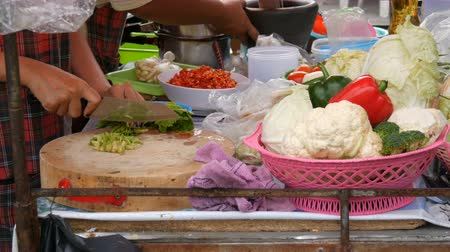maso : Woman cuts greens on a kitchen board with a large knife. Next to vegetables and cooking utensils. Thai street food
