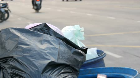 buried : Full clogged trash can with plastic bags leftovers of food and other waste on a busy street on which cars and motorcycles drive Stock Footage