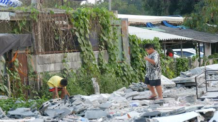 cheerless : PATTAYA, THAILAND - December 16, 2017: Beggar children of a poor gather brick and stones on the streets of the city Stock Footage