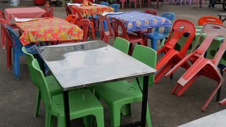 atlanti : Conventional plastic tables and chairs in one of the cheapest cafes in Asia. Multicolored polyethylene tablecloths on plastic tables on the street. Tables chairs and plastic Stock mozgókép