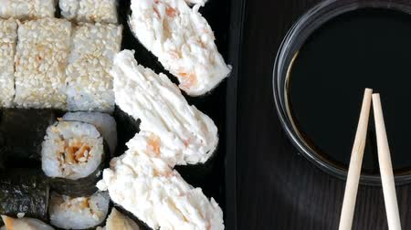нигири : Stylishly laid sushi set on a black wooden background next to soy sauce and Chinese bamboo sticks. Various sushi rolls with salmon, eel, cucumber shrimps and other various stuffing