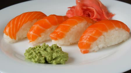васаби : Four large sushi with piece of salmon lie on a large flat plate. Стоковые видеозаписи