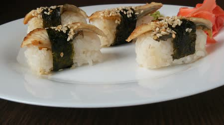 prawns : A large white plate on which lies four huge sushi with eels rewound with a piece of nori next to pink ginger and green wasabi