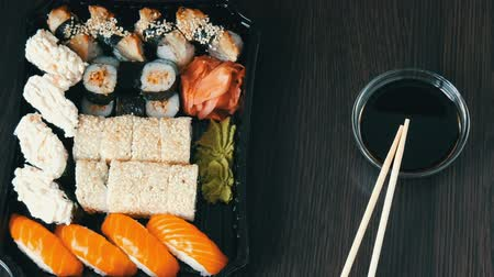 sake : Camera zooms. Stylishly laid sushi set on a black wooden background next to soy sauce and Chinese bamboo sticks. Various sushi rolls with salmon, eel, cucumber shrimps and other various stuffing Stock Footage