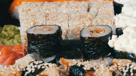 sake : Camera zooms. A lot of different Nigiri Gunkan Maki Sushi with eel salmon Philadelphia cheese cucumber close up view
