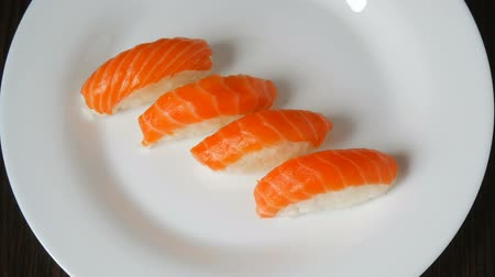 gunkan : On large white plate lie four nigiri with salmon. Japanese food