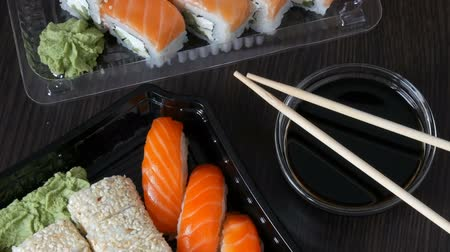 gunkan : Large sushi set with a variety of sushi rolls as well as maki, nigiri, gunkan on a stylish black background. Close to soy sauce and wooden bamboo sticks. Top view