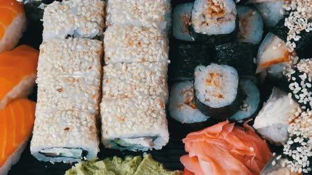 sake : Great choice Variety of sushi roll, nigiri, maki, Gunkan with salmon, eel, shrimps, Philadelphia cheese and other national Japanese cuisine close up Stock Footage