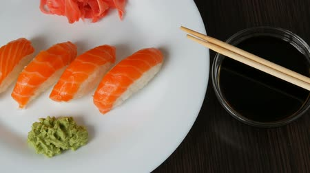 sake : Four large sushi with piece of salmon lie on a large flat plate. Camera zooms Stock Footage