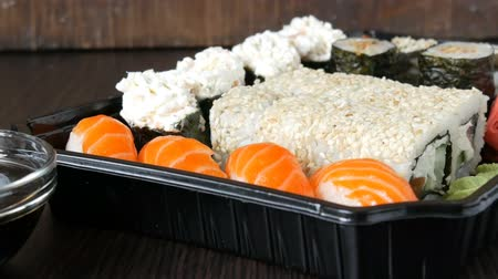 gunkan : Camera zooms. Large sushi set with a variety of sushi rolls as well as maki, nigiri, gunkan on a stylish black wooden background Stock Footage