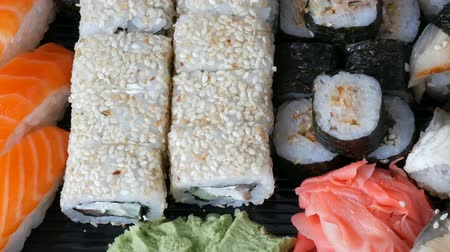 gunkan : Great choice Variety of sushi roll, nigiri, maki, Gunkan with salmon, eel, shrimps, Philadelphia cheese and other national Japanese cuisine close up Stock Footage