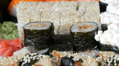 васаби : Camera zooms. A lot of different Nigiri Gunkan Maki Sushi with eel salmon Philadelphia cheese cucumber close up view
