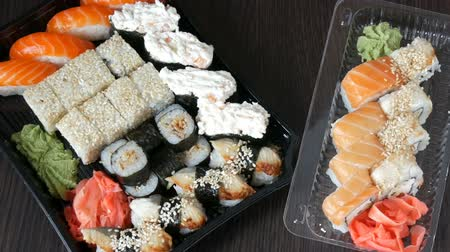gunkan : Two large sushi sets with lots of sushi, roll, maki, nigiri, gunkan. Stylish sushi sets on black wooden table