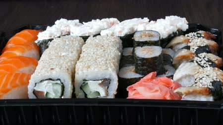 gunkan : Camera zooms stylish fresh sushi set with various kinds of sushi rolls, close up